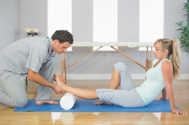 Physiotherapist examining patients foot while sitting on floor