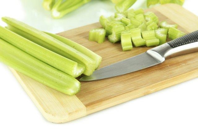 Fresh green celery on cutting board close-up