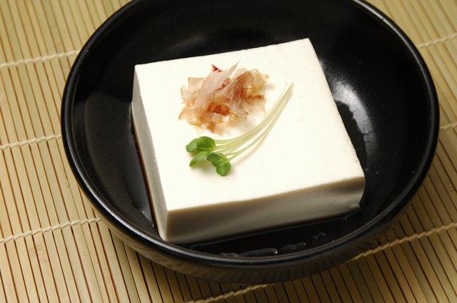 Block of tofu served with a garnish