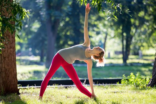 Young slim woman working out outdoors in the park. Doing yoga exercises, stretching on fresh air and enjoying early morning. Healthy lifestyle.