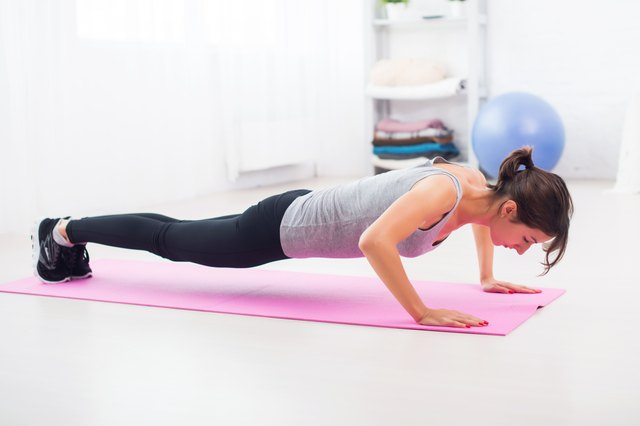 fit woman doing push-ups on the floor in her