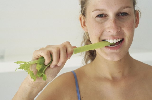 Young woman eating lettuce