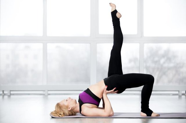 Fitness, stretching workout, attractive mature woman in violet sportswear working out in sports club, keeping fit, doing backbend pose, one-legged shoulder bridge exercise in class, full length