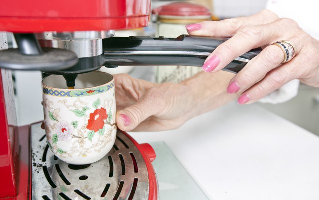 Cropped image of woman dispensing coffee from machine in kitchen