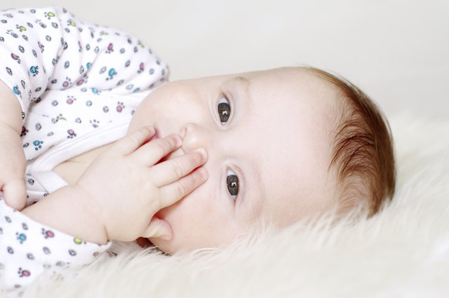 five-months baby closes mouth with hand