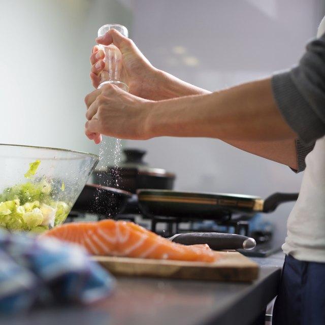 Young woman seasoning a salmon filet