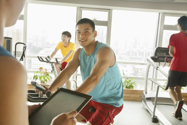 Young man on stationary bike exercising with his personal trainer
