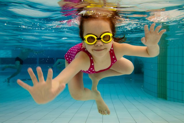 Girl smiles, swimming under water in the pool