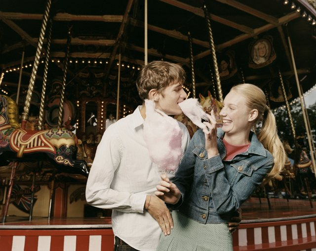Teenage Couple Stand in Front of a Carousel, Girl Feeding Her Boyfriend Candy Floss and Laughing