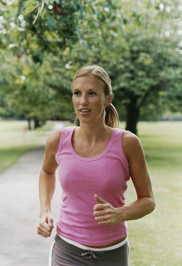 Woman Wearing a Pink Vest Jogging Through a Park