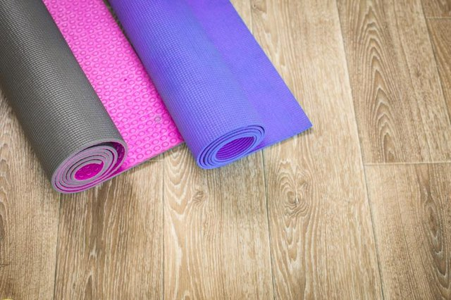 Two Yoga mats (pink and purple) on a wooden background