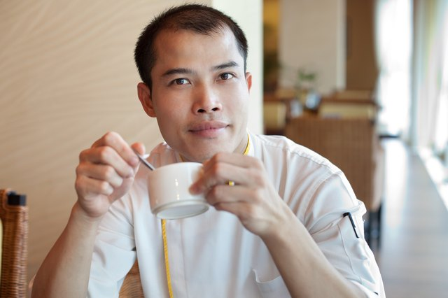Chinese chef wearing uniform enjoying coffee break in restaurant cafe