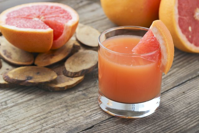 Grapefruit juice and slices on a wooden table