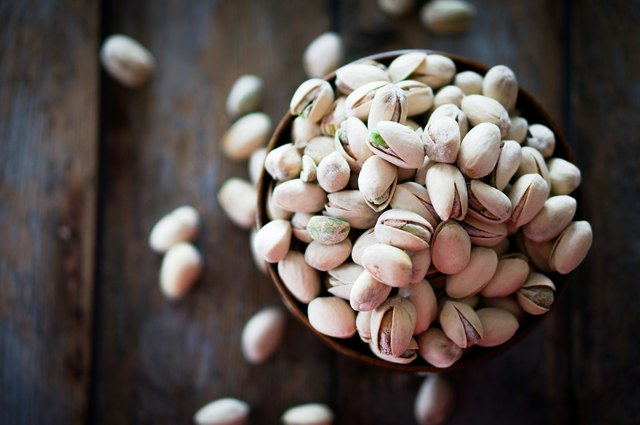 Close-up of roasted pistachios on wooden background