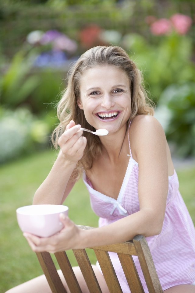 Portrait of young woman eating outdoors, smiling