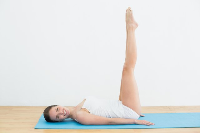 Smiling woman stretching legs on exercise mat