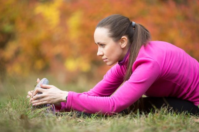 Sporty beautiful young woman practicing yoga, doing seated Hamstring Stretch, forward bend pose, paschimothanasana, stretching before running routine, working out outdoors on autumn day. Side view