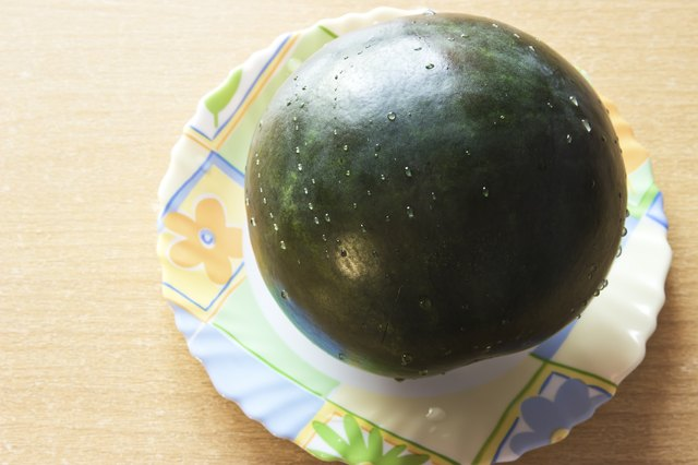 Fresh watermelon on the plate at wooden background