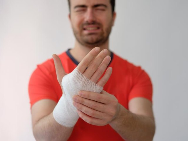 sport man with bandages medication on his hand suffering after a sport injury