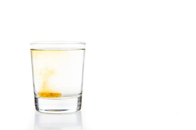 Effervescent vitamin C tablet bubbles in glass of water