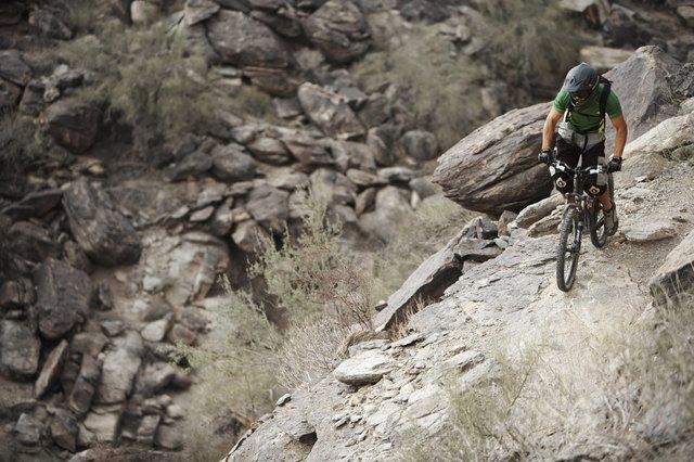 Rider mountain biking along cliff
