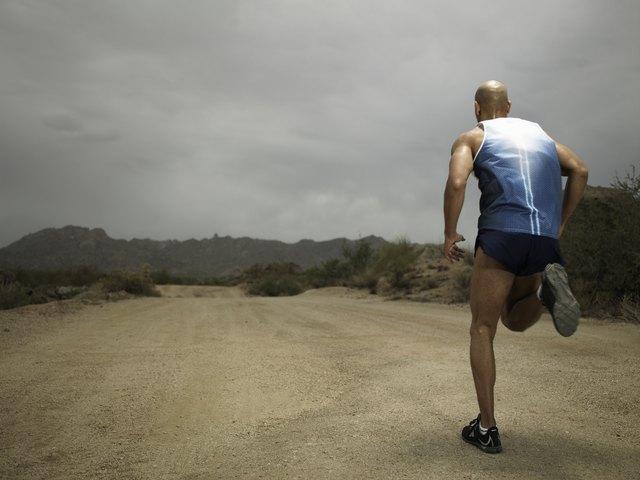 Young man jogging along dirt road, rear view