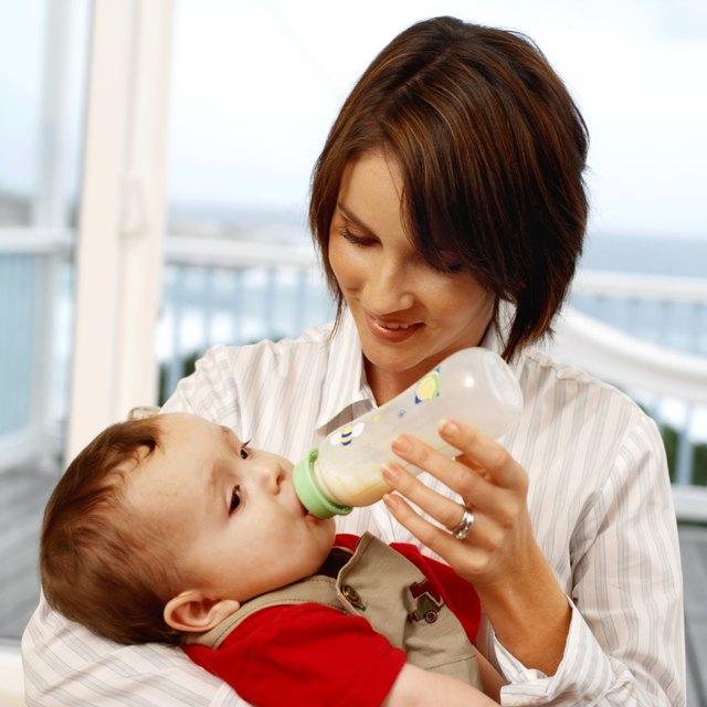 mother bottle feeding baby son (6-12 months)
