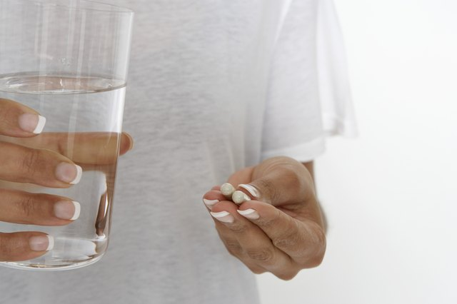Woman holding pills and glass of water, mid section