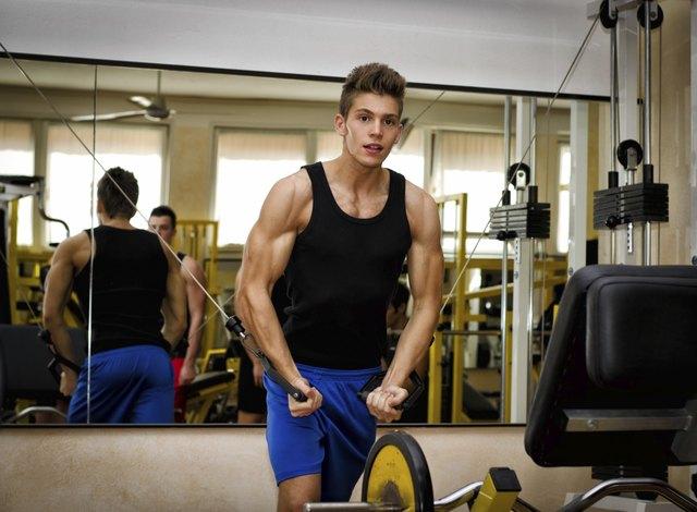 Teen bodybuilder exercising pecs muscles with gym equipment