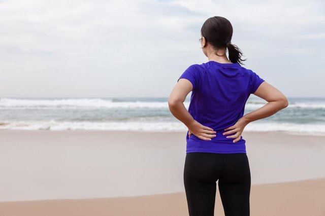 Female athlete suffering from a back injury at the beach on an Autumn day.