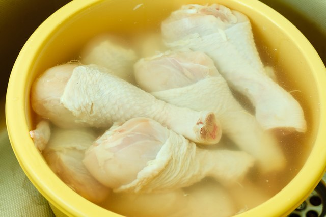 Close up raw chicken meat drumstick in water