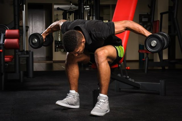 handsome young african descent mixed race man doing Seated Bent Over Dumbbell Reverse Fly workout in gym