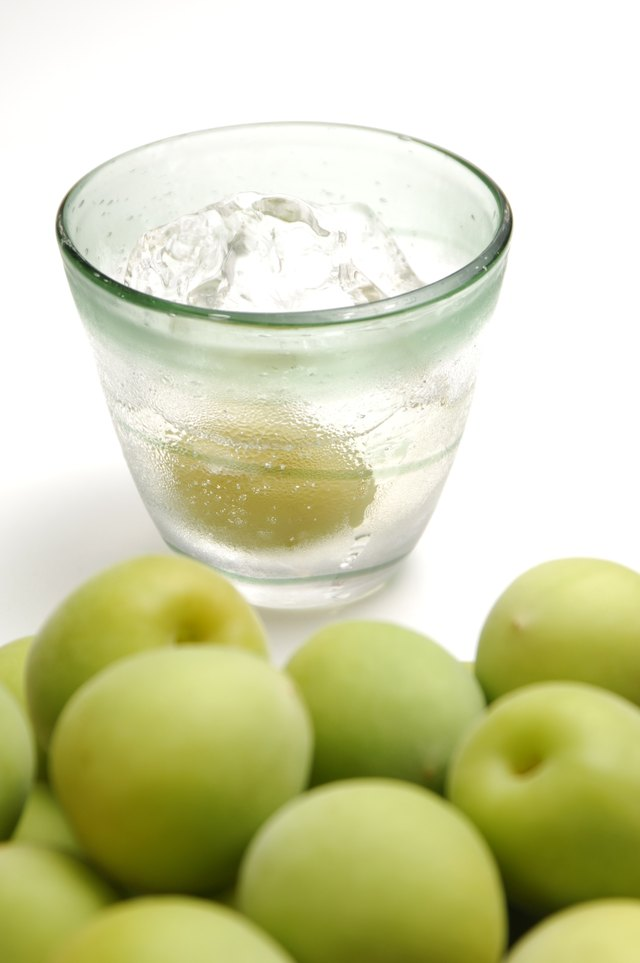 Unripe plums and glass of plum liquor.