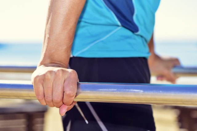 closeup of a young caucasian sportsman wearing sport clothes doing doing dips in parallel bars outdoors