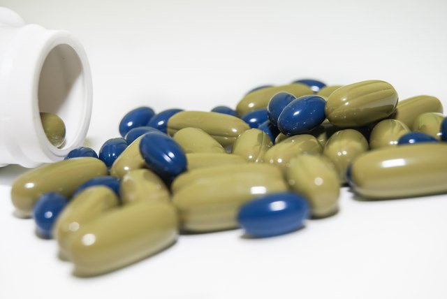 Blue and green pills pouring out of the bottle isolated