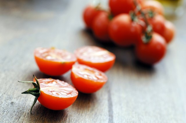 mini sliced halved cherry tomatoes against oak background