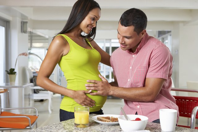 Pregnant Woman And Husband Having Breakfast In Kitchen