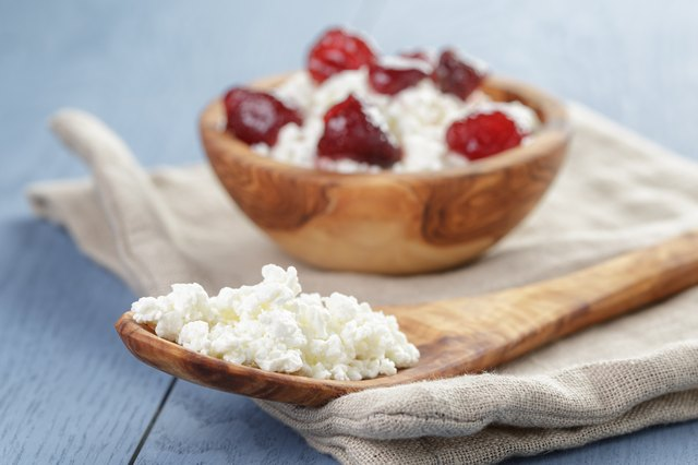 cottage cheese with preserved strawberry on blue table,