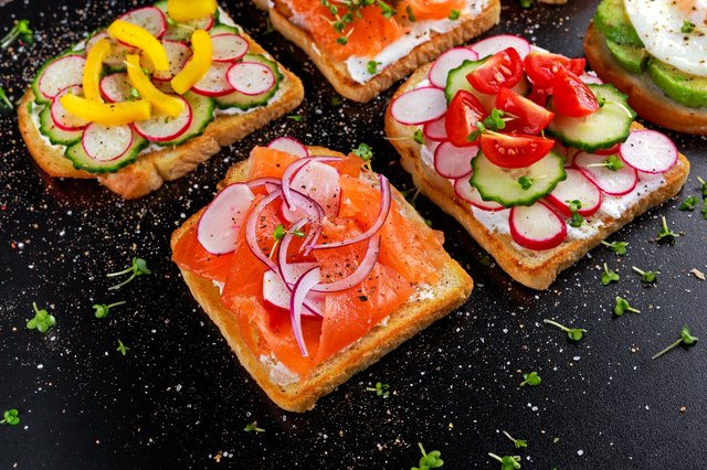 Variety of vegetarian toast sandwiches with salmon, raddish, tomatoes, cucumber