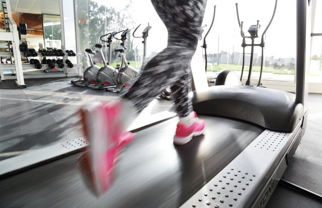 Woman's legs running on treadmill in gym