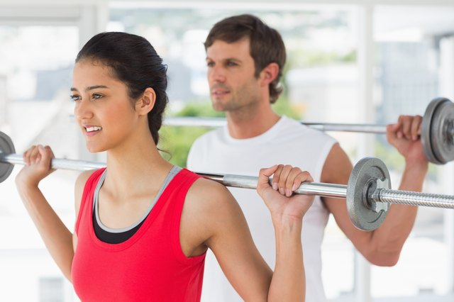 Fit young couple lifting barbells in gym