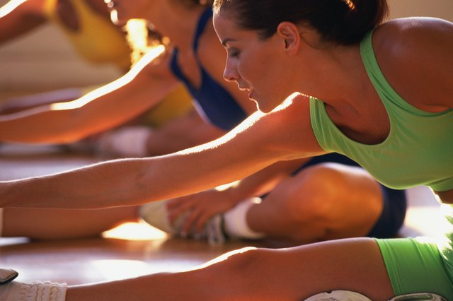 Woman doing floor stretches in fitness class, two women in background