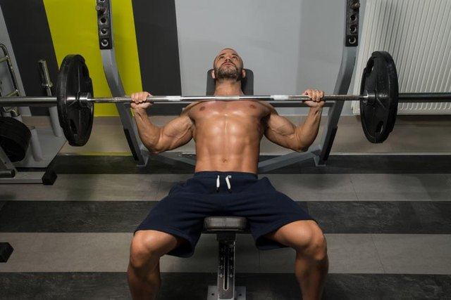 Young Man In Gym Exercising Chest On The Bench Press