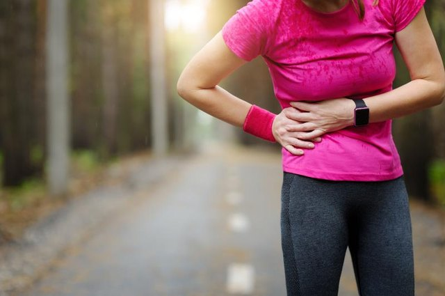 Side stitch - woman runner side cramps. Marathon.