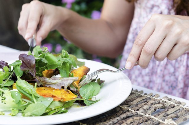 Woman hands and green salad during a meal