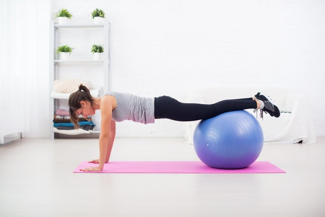 Woman doing push-ups on the floor with fit ball