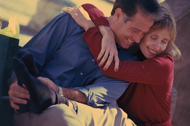 Woman sitting and hugging man, man rubbing her feet