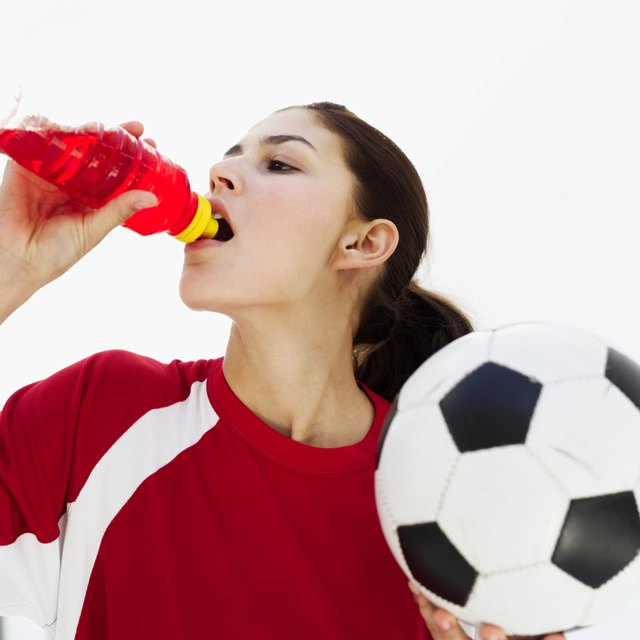 Woman holding a football and drinking juice from a bottle