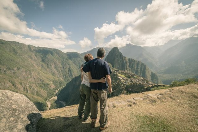 Hugging couple standing in contemplation on the terraces above Machu Picchu, the most visited travel destination in Peru. Rear view, toned, desaturated and vintage styled image.