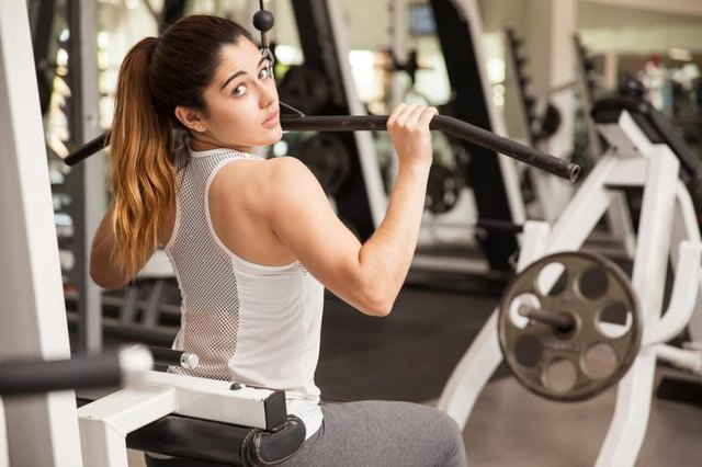 Rear view portrait of a gorgeous strong woman exercising her muscles at the gym and making eye contact
